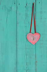 Heart and lock hanging by ribbon on wood background