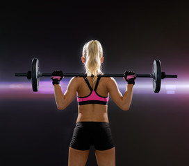 sporty woman exercising with barbell from back