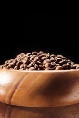 Brightly Lit Wooden Bowl With Aromatic Coffee Beans. Over Black