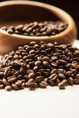 Closeup of Blurred Wodden Bowl With Roasted Coffee Beans Over Bl