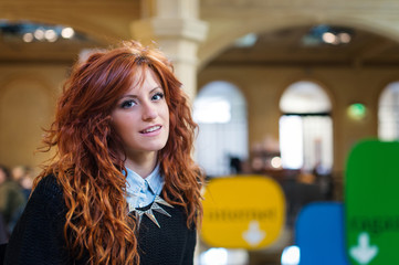 Portrait of young smiling redhead woman inside public library.