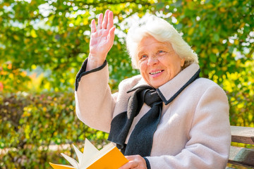 Happy gray-haired woman of 80 years with a book