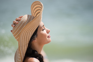 Portrait of a beautiful girl with a big hat at the beach