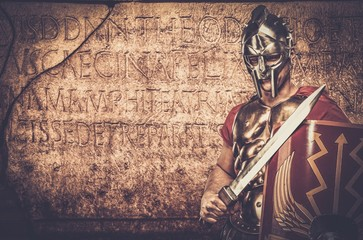 Roman legionary soldier in front of  wall with ancient writing Wall mural