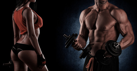 Bodybuilding. Strong man and a woman posing on a black backgroun
