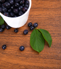 blueberries with leaf in bowl, cup on wooden background