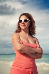 Young smiling woman in red dress on the ocean coast