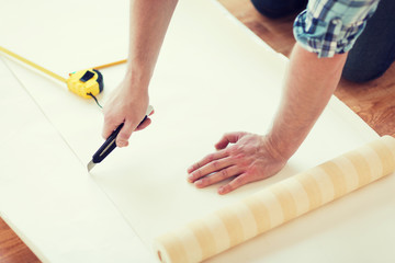 close up of male hands cutting wallpaper