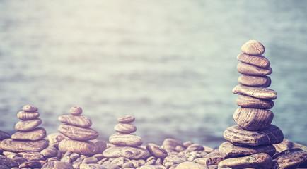 Vintage retro style image of stones on beach, spa concept.