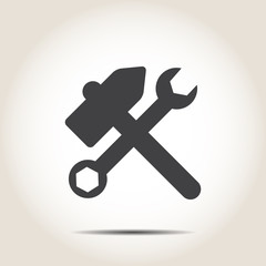 Hammer and wrench on a gray background
