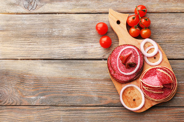 Fototapete - Sliced salami with cherry tomatoes, onion and spices