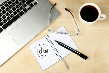 Cup of coffee with note Idea in notebook and glasses