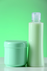Cosmetic bottles on light green background