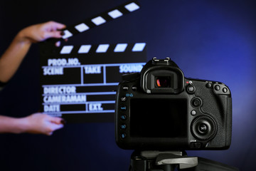 Hands with movie clapper board in front of camera