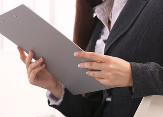 Young  businesswoman in office holding a folder