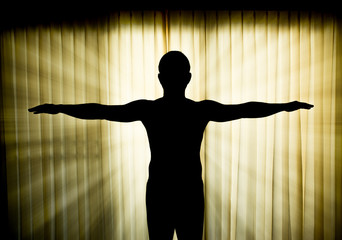 Silhouette man showing hands like a cross with light ray effect