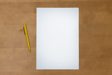 Pen and blank paper sheet on a wooden table
