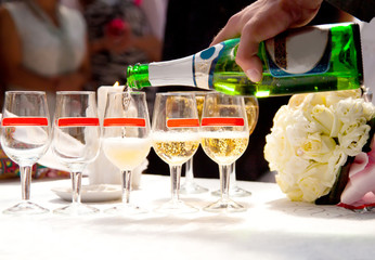man fill in champagne glasses on wedding party