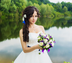beautiful bride with a wedding bouquet on a background of lake