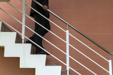 businessman walk down stair, demote,demote,suppress, defame, pre