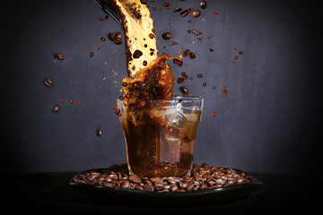 Coffee beans and coffee splashing in a glass on a dark backgroun
