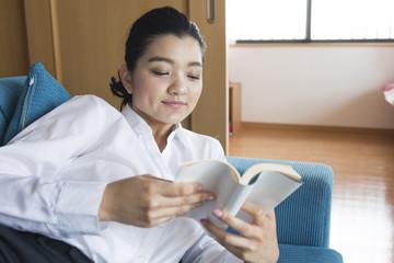 部屋で読書をするOL