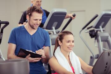 fitness-trainer notiert ergebnisse in den unterlagen
