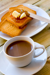 Breakfast time: cup of milky coffee, rusks with butter and jam