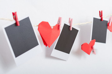 Origami heart and instant photos hanging on clothesline