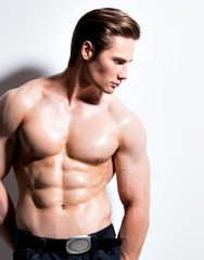 Handsome muscular young man looking sideways.