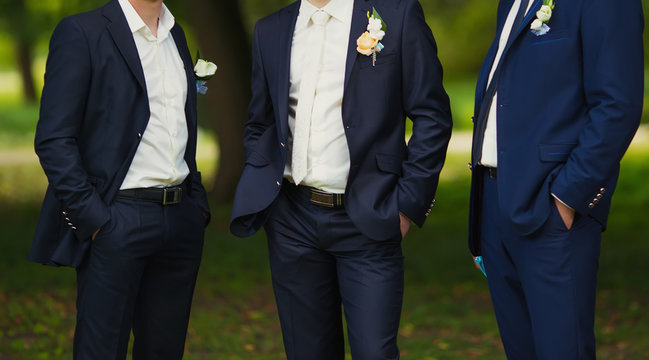 three groomsmen at a wedding in the green park