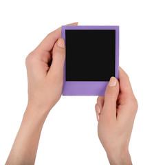 Hands hold polaroid frame