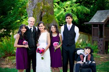 Interracial wedding. Groom standing with his biracial bride's br