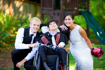 Biracial bride and groom with her little disabled brother in whe