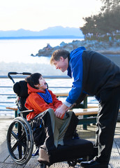 Handsome father talking with disabled biracial son outdoors by l
