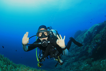 Young woman scuba diving signals okay