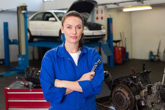 Mechanic looking at camera holding wrench