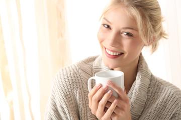 Junge Frau mit einer Teetasse in der Hand