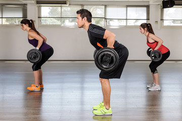 Group of people doing fitness exercises: body pump
