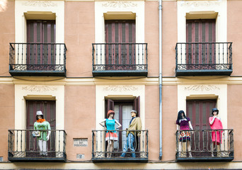 Building with dresed manequins on balconies on a street of Madri