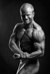 The muscular male bodybuilder flexing biceps