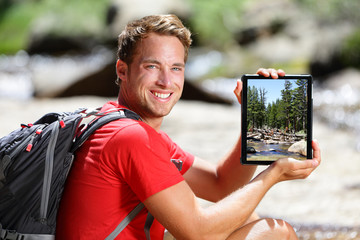 Hiking man showing nature forest picture on tablet
