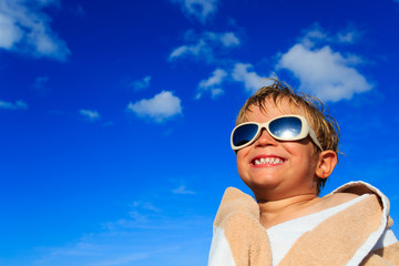 little boy laugh wrapped in beach towel on sky