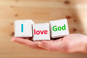 I love God text spelled in cubes on wooden background
