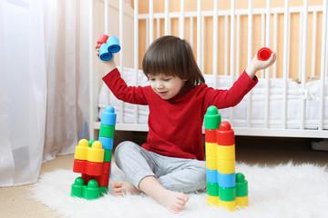Happy 2 years toddler playing plastic blocks