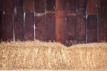 Pile of straw infront of wooden wall