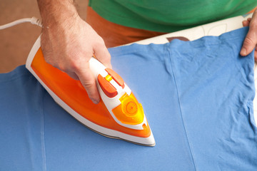 Man ironing clothes on the board