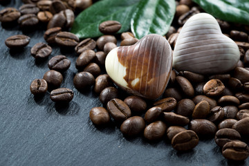 coffee beans and chocolate candies on a dark background, closeup