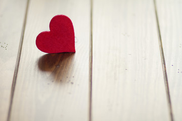 Valentine's day. A red hearts on a brown wooden table. Vintage.