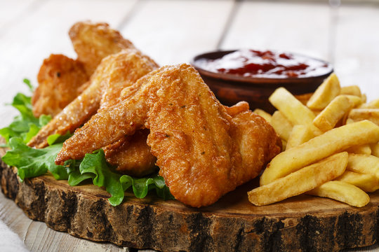 Fried chicken wings with sauce and French fries